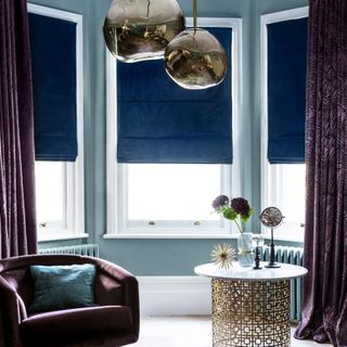 Living room with Broadleigh Aubergine curtains and Radiance Midnight Roman blinds at the window