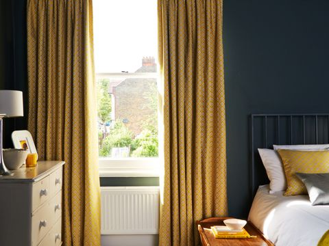A bedroom with a sash window fitted with Yellow Curtains in Eclipse Mimosa fabric