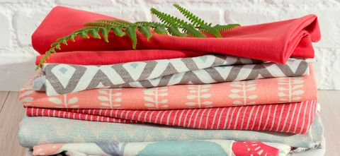 Pile of fabrics in salmon pinks, coral, greys and blues from the Natur collection and Pantone Colour of the Year