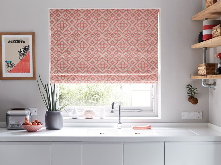 Patterned Harran Coral Roman blind hanging in kitchen