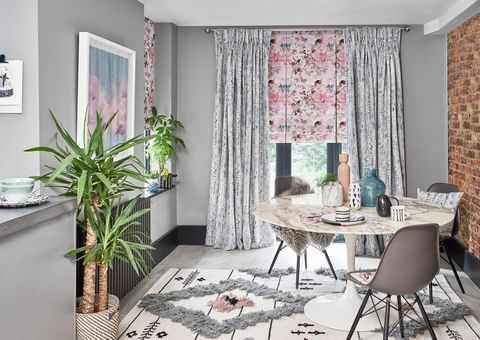 Floral Roman blind with velvet curtains hanging in a luxury dining room