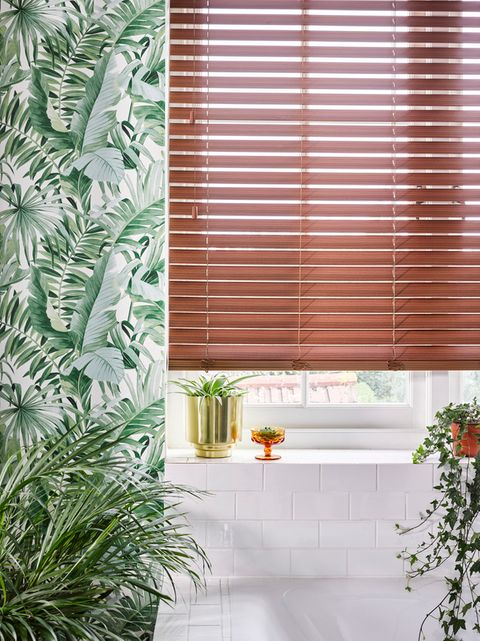 Nutmeg Faux Wood blinds hung in a leafy bathroom