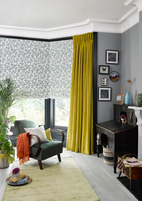 Delizia Teal Roman blinds and Lyon Sulphur curtains hanging in a cosy living room