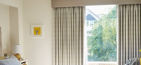 A bedroom with Wallace Chartreuse curtains fitted to the window with header