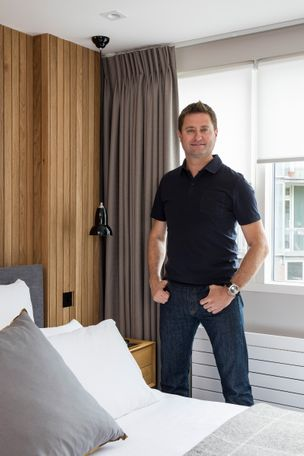 Acacia Ice motorised roller blinds fitted to rectangular windows and paired with bardot grey curtains in a bedroom with George Clarke standing front and centre