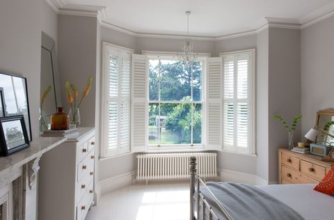 A large bay window in a bedroom is covered by a white wooden Shutter