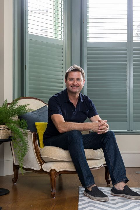 Modern teal Shutters sit behind George Clarke in a traditional living space