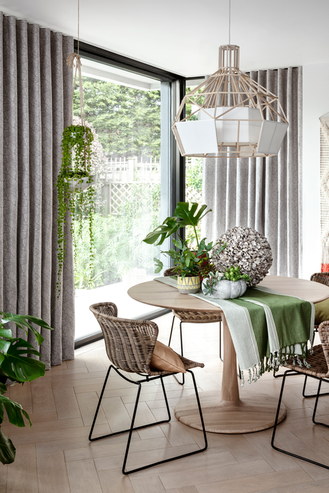 Echo Zinc curtains hanging in a dining room filled with plants