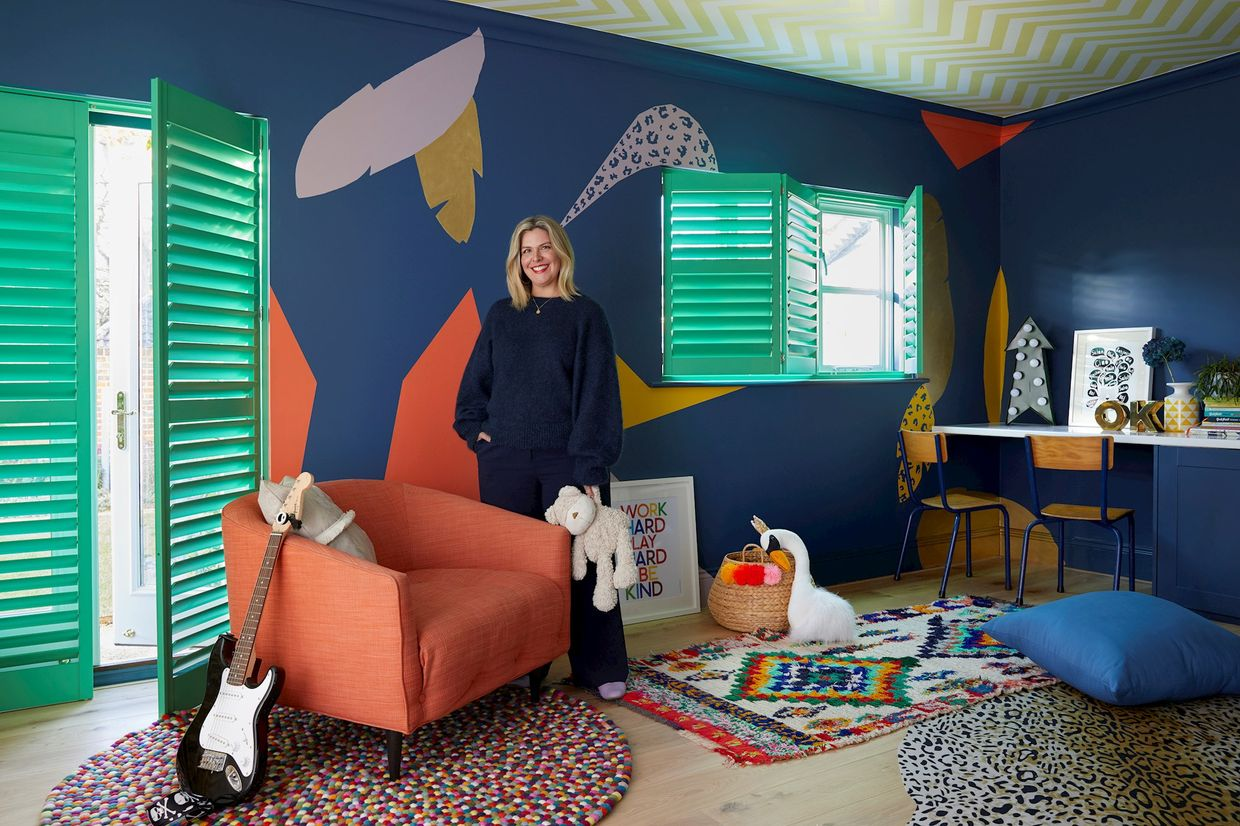 Erica Davies standing in front of custom colour shutters in bright green, fitted in a playroom