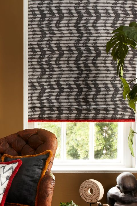 Black and white roman blinds with a zig zag pattern and red fringe is fitted to a rectangular window in a living decorated with brown walls
