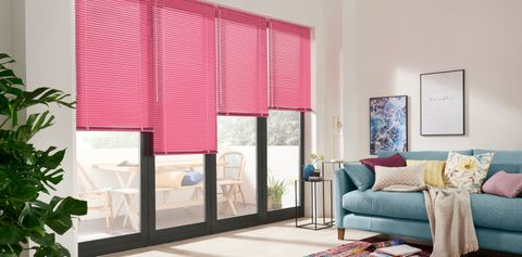 Living room with colourful decor and bifold doors dresed with pink venetian blinds