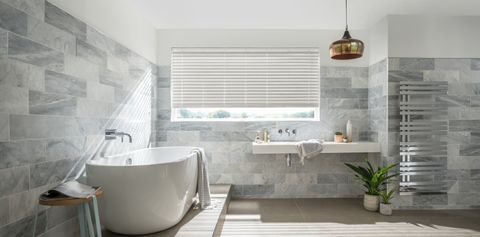 Large bright bathroom with matching grey wooden blinds slightly open to let in light