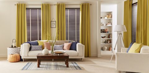 Modern living room with large windows dressed with curtains and faux wooden blinds in dark brown