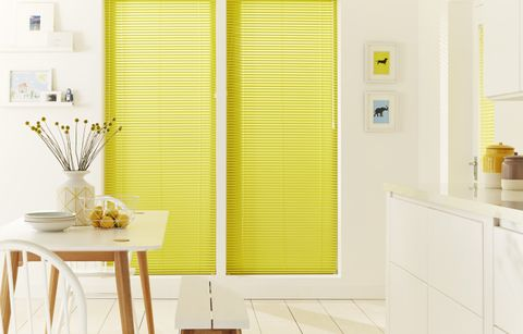 White open plan kitchen diner with contrast yellow venetian blinds