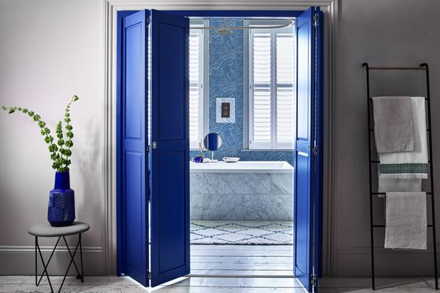 Solid tracked shutters in custom colour blue leading to bathroom