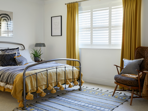 Bedroom with curtains in bright yellow fabric and white shutters in the windows