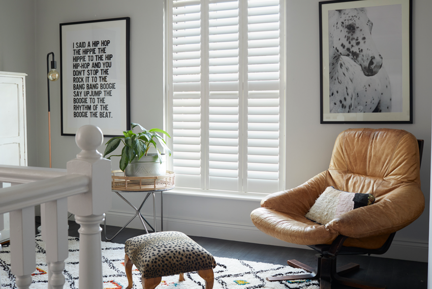 full height silk white shutters made of richmond material installed on windows of wall in  hallway