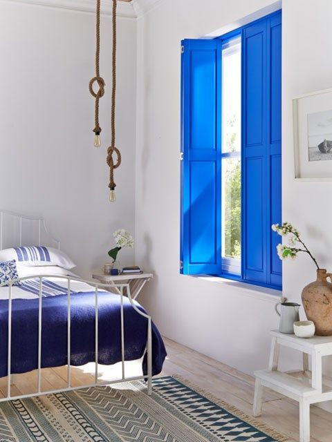 Bright blue solid shutters in bedroom window