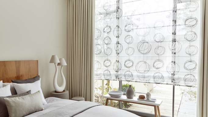 A bedroom with a large window fitted with a Voile Roman blind in Swirl Dusk