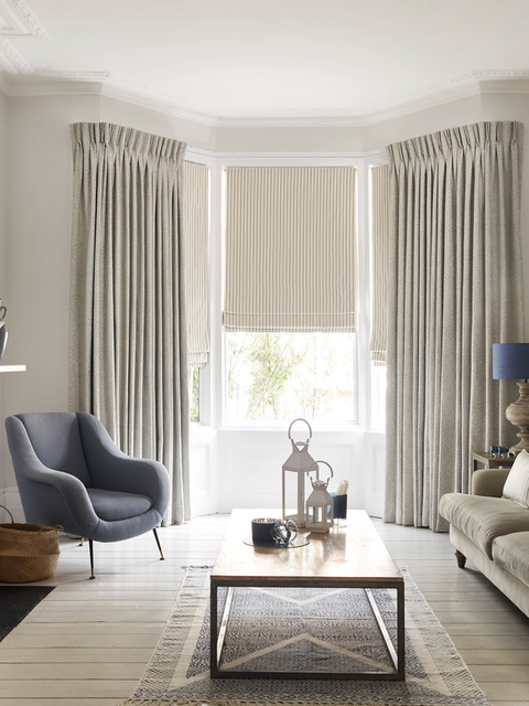 White curtains matched with cream roman blinds are fitted to bay shaped windows in a living room decorated in white