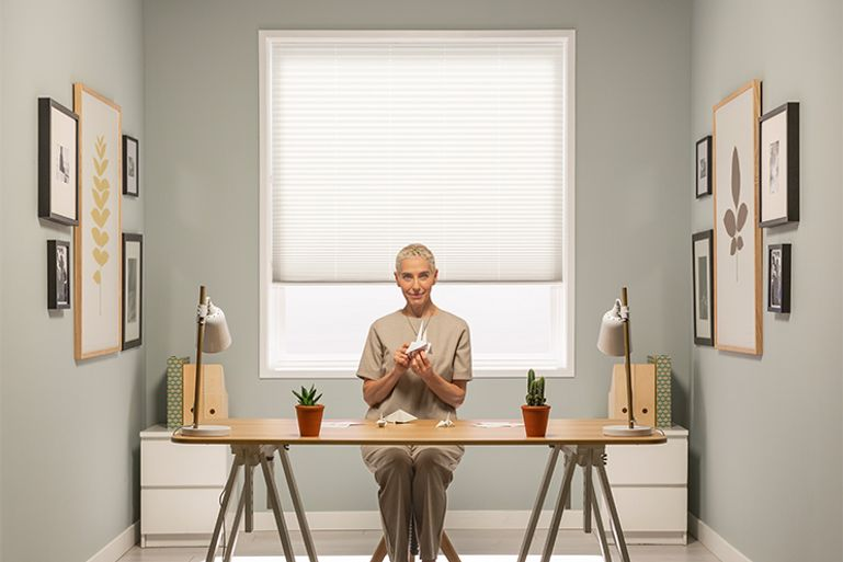 Woman sitting in front of pure white pleated blind from Hillarys advert