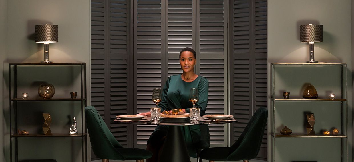 Image of woman smiling at dining table from Hillarys advert