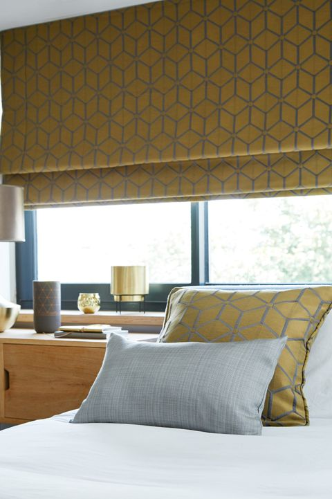 Nexus Brushed Gold Romans blind above a bed
