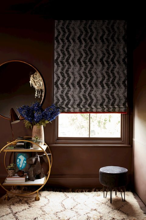 Cadillac Noir Roman blind with crimson fringing in a hallway