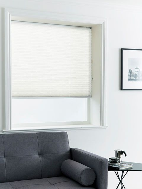 Pleated white blinds hanging in a living room