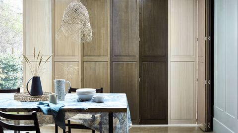 Ombre natural wood shutters in a dining room window