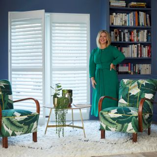 Erica Davies in front of white shutters in a blue living room with 2 arm chairs in green leaf patterned fabric