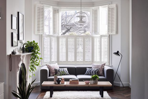 modern stylish living room with full height white shutters in a bay window
