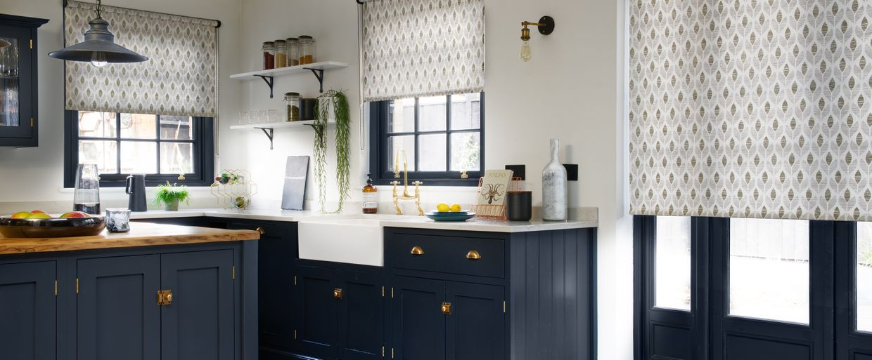 patterned grey roller blinds in a kitchen with deep blue units