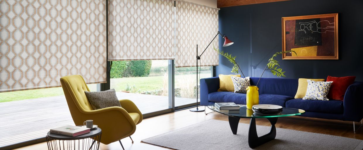 modern living room with stylish geometric print cream roller blinds in a patio window