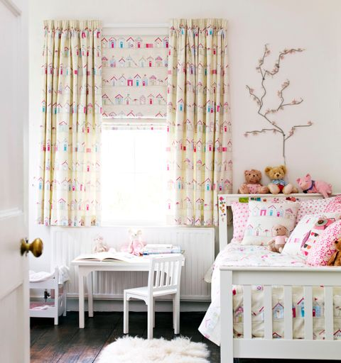 Beach Huts Pink Roman blind overlaid with Beach Huts Pink curtains in children's room