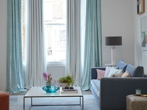 Pastel mint green and white curtains hanging in a modern living room