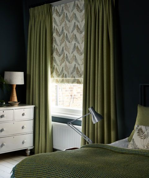 Green plain curtains over leaf motif Roman blind in bedroom