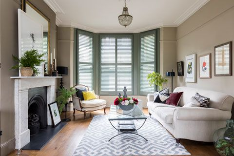 Living room with custom colour shutters in bay window