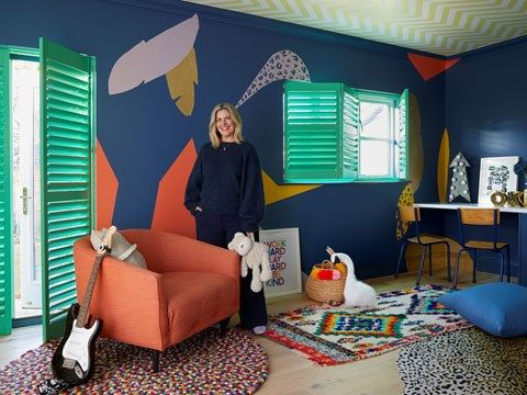 Erica Davies standing in a vivid child's playroom fitted with bright green shutters