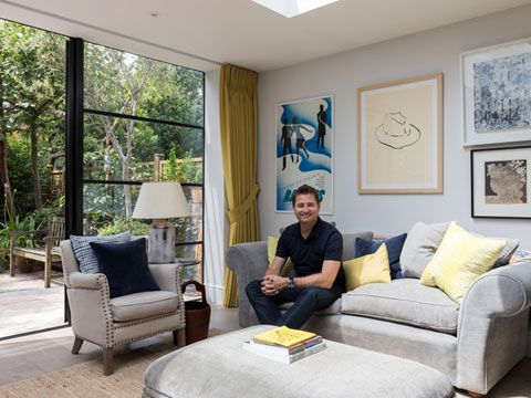 George Clarke in front of Crittal windows and Tetbury Mustard curtains