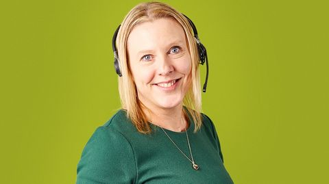 A photo of someone with a head set against a green background