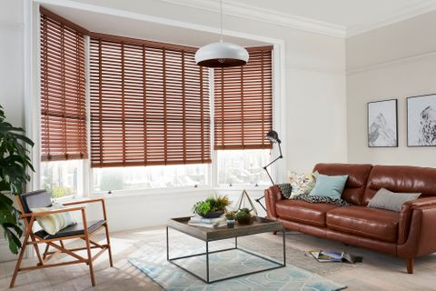 Stylish living room with faux-wood blinds in natural wood stain