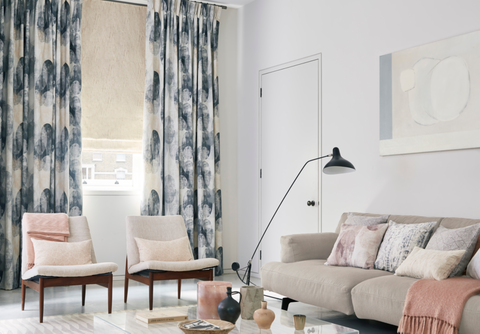 Relaxed living room with fade-out print curtains and cream Roman blinds
