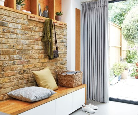 Boot room with exposed brickwork and dove grey curtains