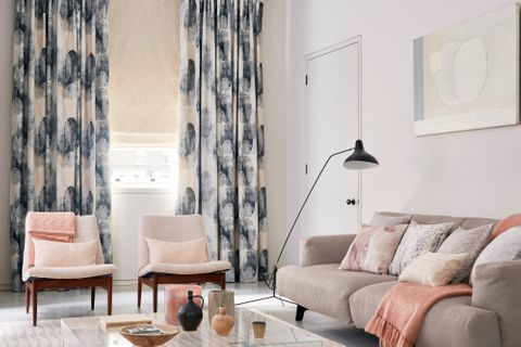Living room with circle print curtains over a cream Roman blind
