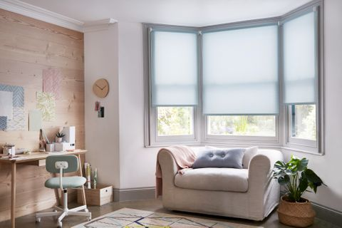Living room bay window with pale blue Roller blind