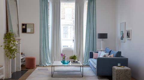 Mint green and white curtains hanging in a large living room bay window