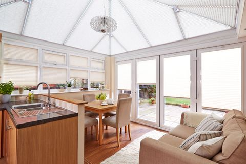 Bright open plan kitchen and dining area with white pleated conservatory blinds