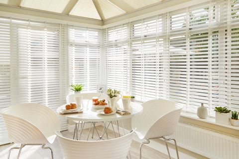 Bright dining area in a conservatory with White Faux Wood conservatory blinds and pleated conservatory roof blinds