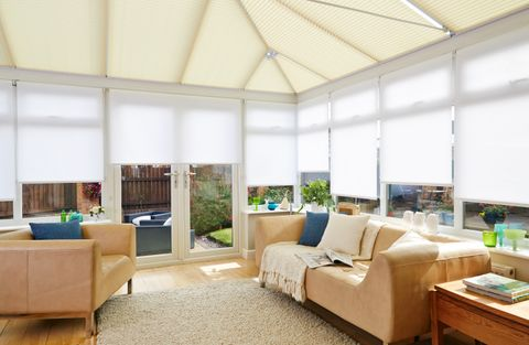 Cosy living area in a conservatory with Sand Pleated conservatory roof blinds and White roller conservatory side blinds